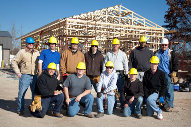 PWSC Home Builders in front of a home under construction.